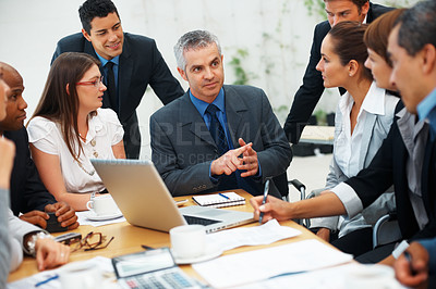 Buy stock photo Confident male leader surrounded by colleagues at table during meeting