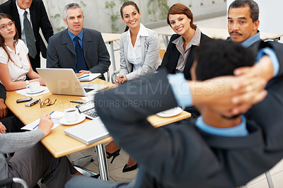 Buy stock photo Focus on colleagues looking at relaxed executive during meeting