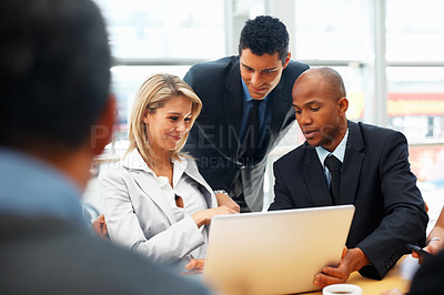 Buy stock photo Shot of a group of business people looking at a laptop together