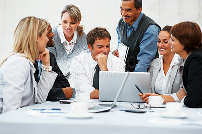 Buy stock photo Group of executives sitting around a laptop computer