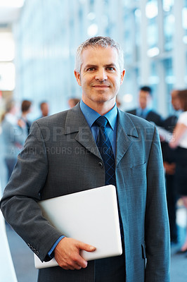 Buy stock photo Portrait of smiling senior executive holding laptop