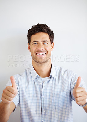 Buy stock photo Portrait of a young handsome guy showing goodluck sign against grey background