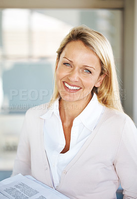 Buy stock photo Portrait of an attractive young businesswoman holding some papers in hand smiling