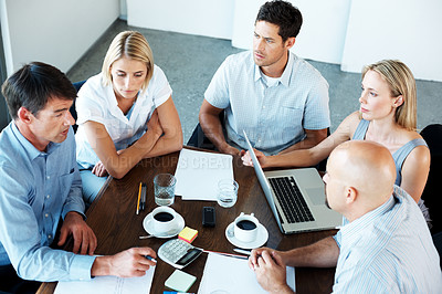 Buy stock photo Top view of working business group sitting at a table during a corporate meeting