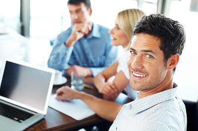 Buy stock photo Smart young business executive with colleagues discussing in the background in a meeting