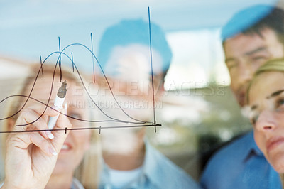 Buy stock photo Confident businesswoman drawing a chart to illustrate market fluctuations