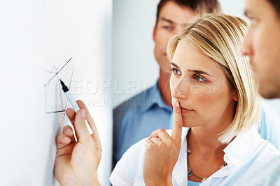 Buy stock photo A smart young businesswoman looking carefully at a diagram alongside her colleagues