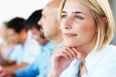 Buy stock photo Young business woman looking away in thought while sitting in a conference with her associates