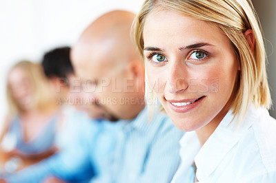 Buy stock photo Closeup of a cute young businesswoman smiling in a meeting with her colleagues in background