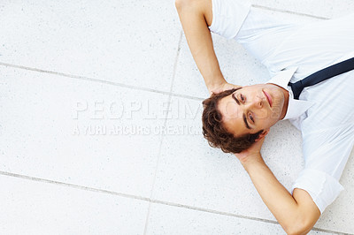 Buy stock photo Top view of a young businessman lying on a white tiled floor with his hands behind his head - copyspace