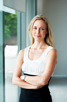 Buy stock photo Portrait of a smiling young casual businesswoman standing with her hand folded