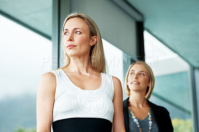 Buy stock photo Portrait of a successful business woman looking away with a colleague in background