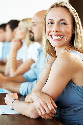 Buy stock photo Portrait of a smiliing young businesswoman sitting with her colleagues in a meeting at office