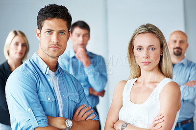 Buy stock photo Portrait of smart young man and woman standing in front of some people at the back
