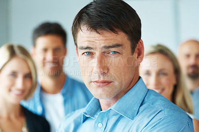 Buy stock photo Closeup portrait of a handsome young businessman looking with attitude people in background