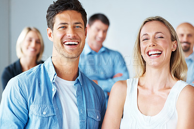 Buy stock photo Portrait of a casual business man and woman smiling together with colleague in background