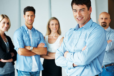 Buy stock photo Portrait of a confident business team standing and smiling with folded hand at office