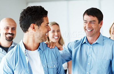 Buy stock photo Portrait of a happy young business man standing with friendly colleague hand on his shoulder