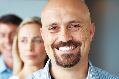 Buy stock photo Portrait of a smiling businessman standing in a line with colleagues at office