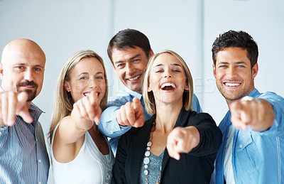 Buy stock photo A group of successful business people pointing towards you and smiling
