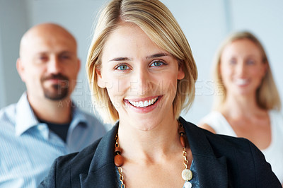 Buy stock photo Portrait of a pretty young businesswoman smiling with her colleagues in the background