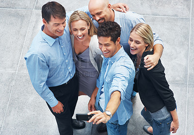 Buy stock photo Top view of young man standing with colleagues and taking self portrait