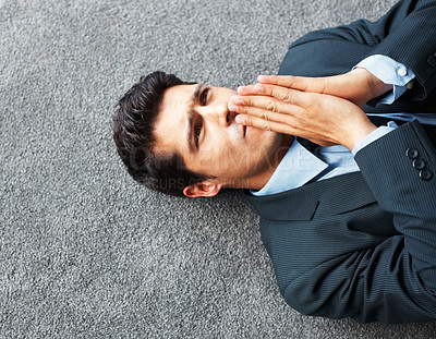 Buy stock photo Top view of executive lying on floor with finger on lips