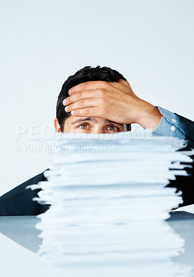 Buy stock photo Discouraged business man with a stack paper in front of him