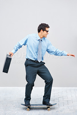 Buy stock photo Handsome business man with briefcase skateboarding to work