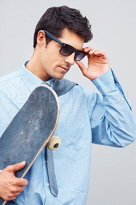 Buy stock photo Business man adjusting sunglasses while holding skateboard
