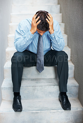 Buy stock photo Businessman sitting on steps, looking down with hands on head