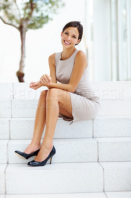 Buy stock photo Portrait of lovely young female sitting on steps and smiling