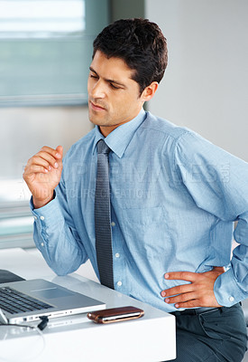 Buy stock photo Businessman stretching while seated at desk