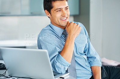 Buy stock photo View of businessman sitting next to laptop and looking off into distance