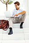 Young businessman sitting on steps and working on laptop