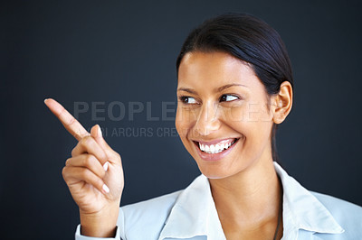 Buy stock photo View of female executive pointing at something while smiling
