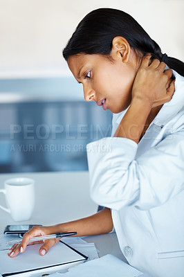 Buy stock photo View of business woman appearing stressed while reviewing notes