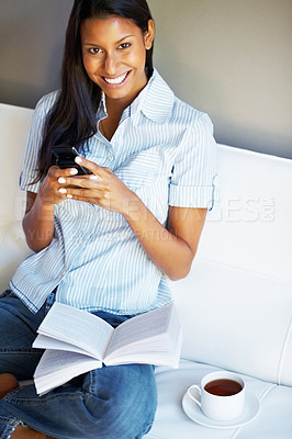Buy stock photo Pretty woman sitting on sofa holding cell phone