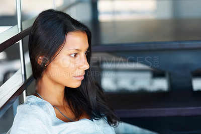 Buy stock photo Attractive woman sitting indoors while looking into distance