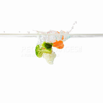 Buy stock photo View of broccoli and carrots falling into water against white background