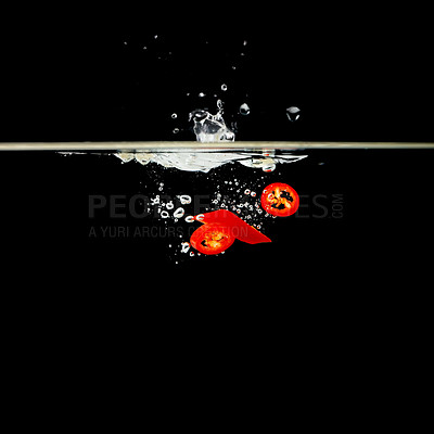 Buy stock photo Slices of chili peppers underwater against black background