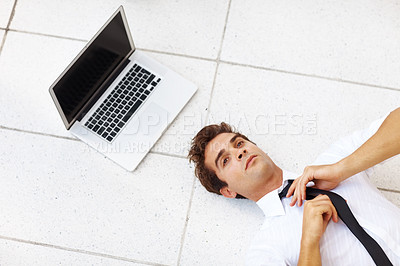 Buy stock photo Top view of young businessman fixing his tie while lying on floor with a laptop