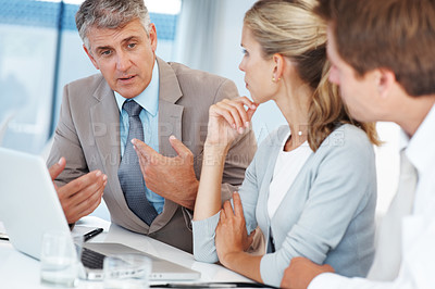 Buy stock photo Portrait of confident business man explaining a project to colleagues at the office