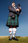 Senior highlander wearing kilt and playing bagpipes