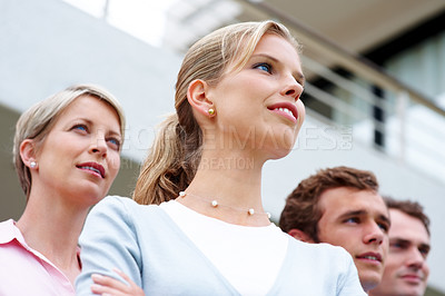 Buy stock photo Young business woman looking away and thinking for future perspective with her associates in background