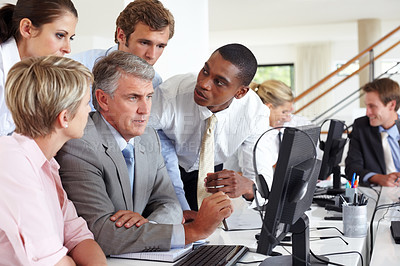 Buy stock photo Senior male business executive guiding his coworkers at a meeting in an office