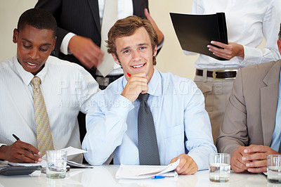 Buy stock photo Handsome young male executive sitting along with his business associates at a meeting