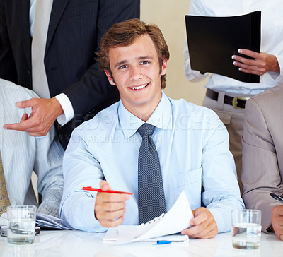 Buy stock photo Portrait of a confident young businessman signing a contract during meeting at office