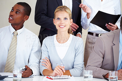 Buy stock photo Beautiful young businesswoman smiling at a meeting with colleagues in the office