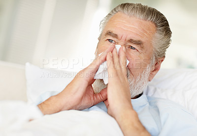 Buy stock photo Shot of a sick senior man blowing his nose into a tissue